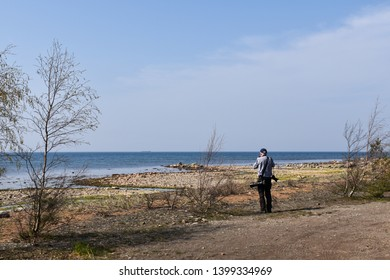 Male photographer standing by the coast of the Baltic Sea at the swedish island Oland