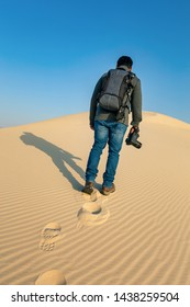A male Photographer step by step walking on Desert Landscape in Abqaiq Dammam Saudi Arabia.