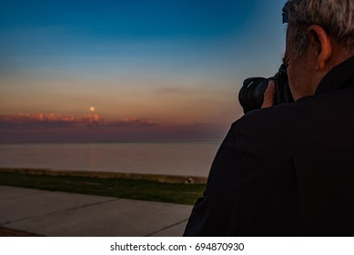 Male Photographer Sunset Moon over Water