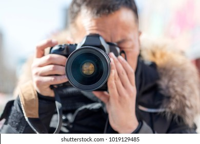 A male photographer takes a camera with a camera