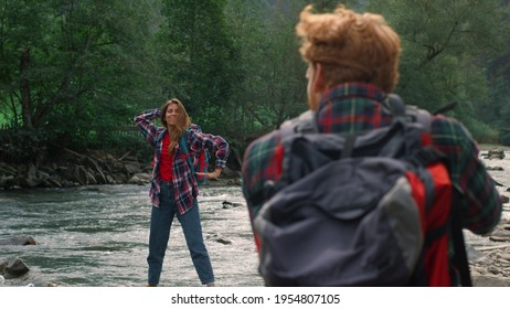 Male photographer taking photos of girl during hike in mountains. Cheerful lady making funny poses during shooting. Redhead man and woman standing at river in mountains