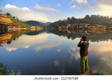 Male photographers are taking photo the water reflection at the Lee wine ruk thai lake, Mae Hong Son in Thailand.This is very popular for photographers and tourists. Attractions and travel concept.