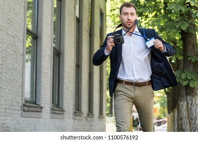 male photojournalist running with digital photo camera and press pass