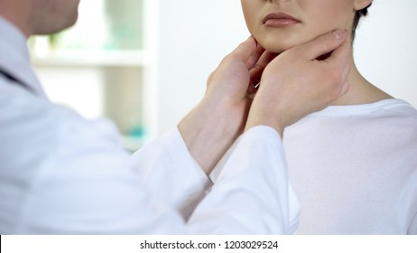 Male physician checking patient throat and neck, health examination in hospital