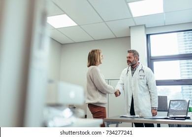 Male physician shaking hands with patient in clinic. Medical professional meeting woman in hospital.