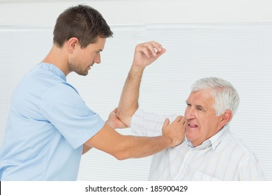 Male physiotherapist assisting senior man to stretch his hand in the medical office