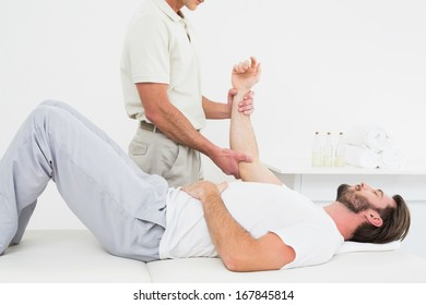 Male physiotherapist examining a young man's hand in the medical office