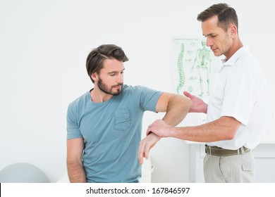 Male physiotherapist examining a young man's arm in the medical office