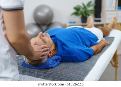 Male physiotherapist giving head massage a senior patient in clinic