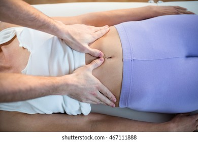 Male physiotherapist giving stomach massage to female patient in clinic