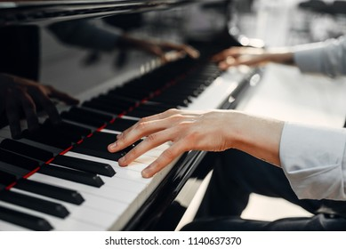 Photo of Male pianist hands on grand piano keyboard