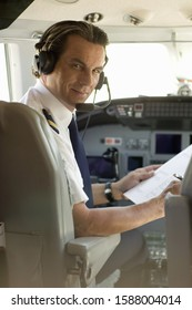 Male pilot smiling in cockpit of airplane