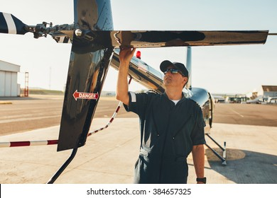 Male pilot in uniform examining helicopter tail wing. Pre flight inspection by pilot at the airport.