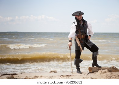 Male pirate with a sword on the seashore