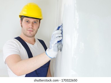Male plasterer in hard hat polishing the wall. Space for text.