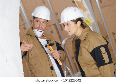 male plasterer pointing a wall to his apprentice