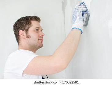 Male plasterer in uniform polishing the wall.