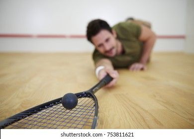 Male player falling on floor while squash game