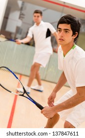 Male players playing a match of squash