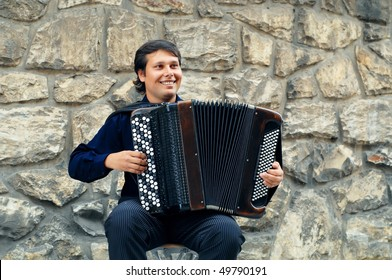 Male playing on the accordion against a grunge background