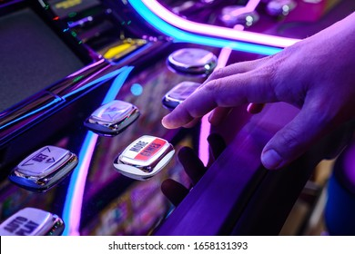 Male Playing Slot Machines In Casino. Close-up Of Male Hand