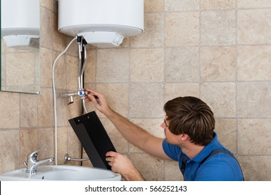 Male Plumber Checking Electric Boiler And Holding Clipboard At Home