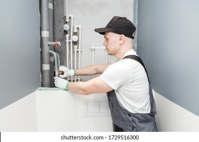Male plumber checks pipes for central hot and cold water supply of apartment.