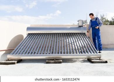 Male Plumber Doing Solar Energy Boiler Inspection