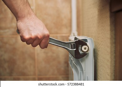 Male Plumber Fixing Radiator With Wrench