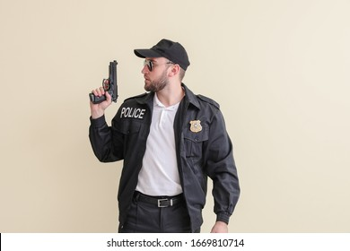 Male police officer with gun on light background