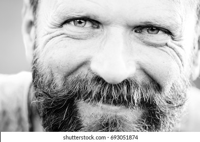 Male portrait. Brutal stylish guy with a beard and mustache. Open, kind look. Wide, kind smile. Looks like a traveler or a monk. Close-up.