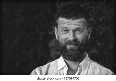 Male portrait. Brutal stylish guy with a beard and mustache. Open, kind look. Wide, kind smile. Looks like a traveler or a monk. Standing in a white shirt against the background of dense trees.