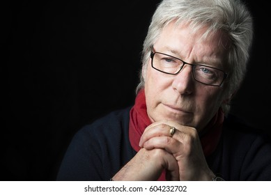 Male portrait close up looking away and thoughtful hands under chin casual but smart wearing glasses
