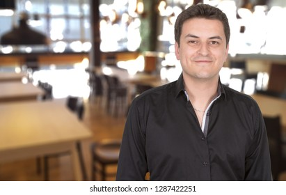 Male portrait of smiling proud owner man standing at his restaurant