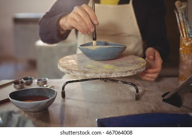 Male potter painting on bowl in workshop