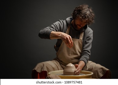 A male potter works with clay on a potter's wheel.
