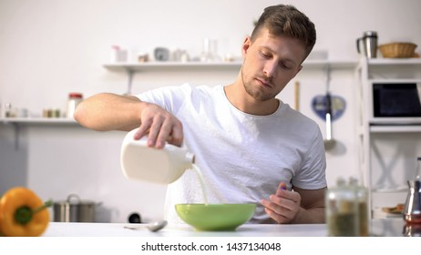 Male pouring milk in bowl with corn flakes, nourishing and healthy breakfast