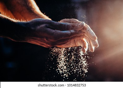 Male powerlifter hand in talc. palm preparation before lifting weights. Toned image. Hands in chalk. with the light different view
