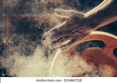 Male powerlifter hand in talc. preparation before lifting weights. Toned image. Hands in chalk. With a barbell view