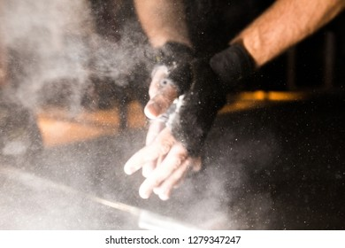 male powerlifter hand in talc and sports wristbands preparing to bench press. blur
