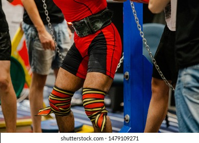 male powerlifter knee wraps squatting competition in powerlifting