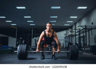 Male powerlifter starting deadlift barbell in gym