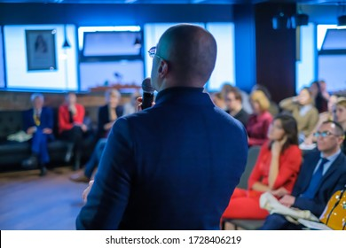 Male presenter speaks to audience at seminar
