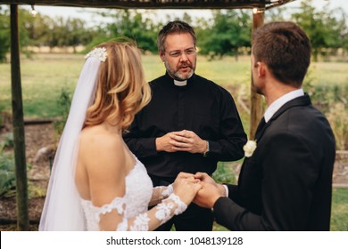 Male priest marries a couple in lovely outdoor wedding ceremony. Wedding ceremony of elegant couple holding hands and taking vows.