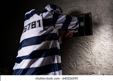 Male prisoner wearing prison uniform tries to escape through the window with bars in a small dark prison cell