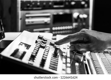male producer, dj fingers adjusting mixing control surface in recording, broadcasting studio, black and white