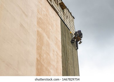 Male produces steeplejack work. Worker repairs the wall of a multi-storey building.