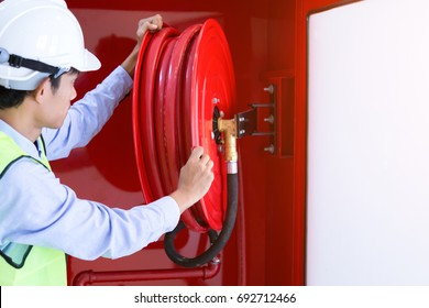 Male Professional checking a fire extinguisher,Fire extinguisher and fire hose reel