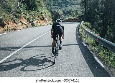 Male professional cyclist climbing in the spanish mountains