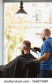 Male professional hairdresser serving client by clipper. Ginger handsome brutal stylish young man with thick big beard and short hair getting trendy haircut in black cape. Light white barber shop